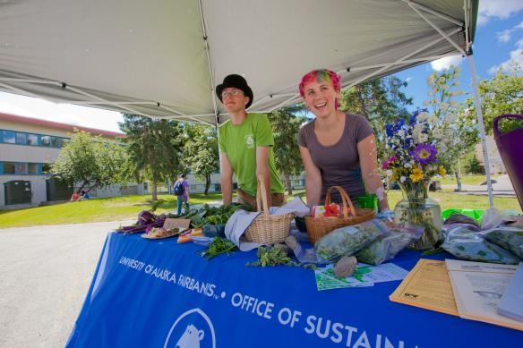 Alexander Bergman, left, and Heather Currey, student employees with UAF's office of sustainability, sell campus-grown vegetables each Thursday this summer in front of Wood Center.
