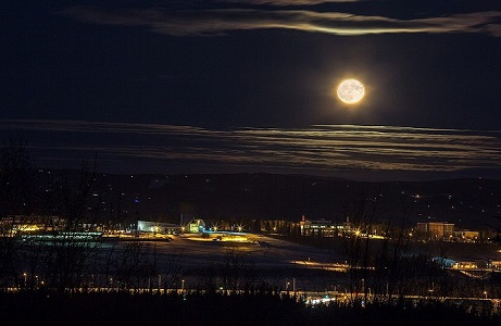 Image of a full moon hanging over UAF Campus, centered on West Ridge, and taken from far away. The image is predominantly dark blue, with orange lights in a line along the campus buildings.