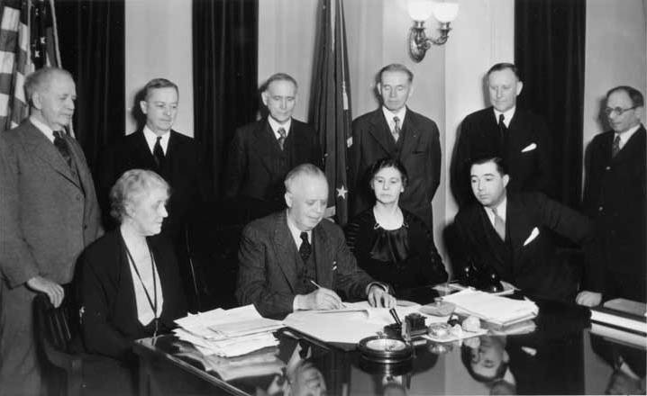 Alaska Governor John Troy signed the bill that changed the Alaska Agricultural College and School of Mines to the University of Alaska. Signing of Bill No. 97. Standing from left to right: James Wickersham, Charles Bunnell, Senate President Luther Hess, Reps./Regents Andrew Nerland and Arthur A Shonbeck, and Speaker of the House J.S. Hofman. Seated: Regent Grace Wickersham, Governor Troy, Regent Harriet Hess, and Rep. George Lingo. Photo: UAF Rasmuson Library, Charles Bunnell Collection