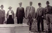 Pictured from left is Judge Wickersham, Harriet Hess, and four other unidentified individuals gathered during the construction of the cornerstone.