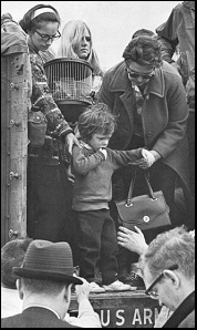 A young evacuee, looking very scared, is helped off a U.S. Army flatbed truck on the UA campus.