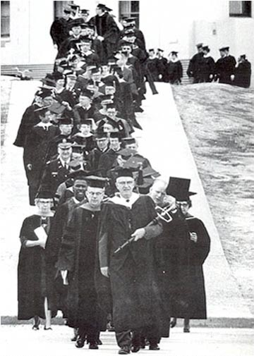 The 1967 commencement parade led by university marshal William Cashen, flanked by Regent Elmer Rasmuson on the left and Dean Earl Beistline on the right. Cashen carried the ceremonial university mace.