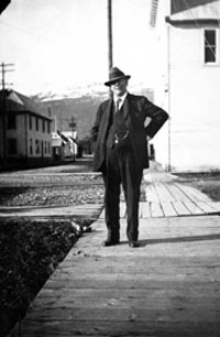 George Love, U.S. Commissioner and insurance agent, in front of his office in the Pioneer Hall, Valdez. Anchorage Musem at Rasmuson Center, Crary-Henderson Collection