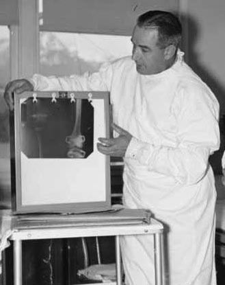 "Dr. Philip Moore study an x-ray of patient during ""rounds"" at Mt. Edgecumbe Medical Center Orthopedic Hospital. Photo: Alaska State Library, Historical Collections"